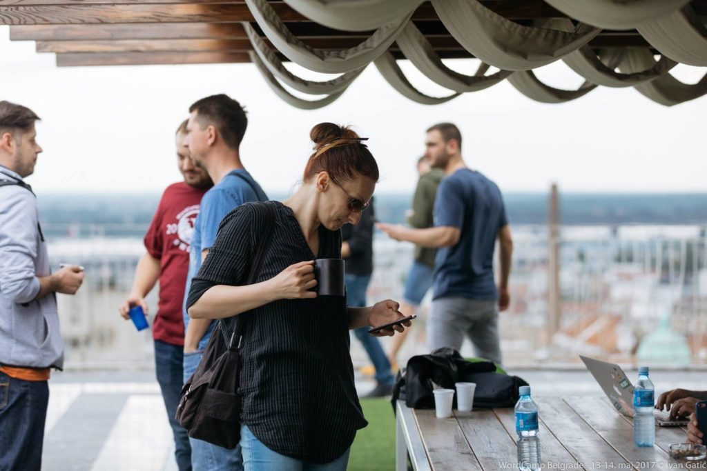 Milana, on a rooftop baclony with some other people looking at her phone