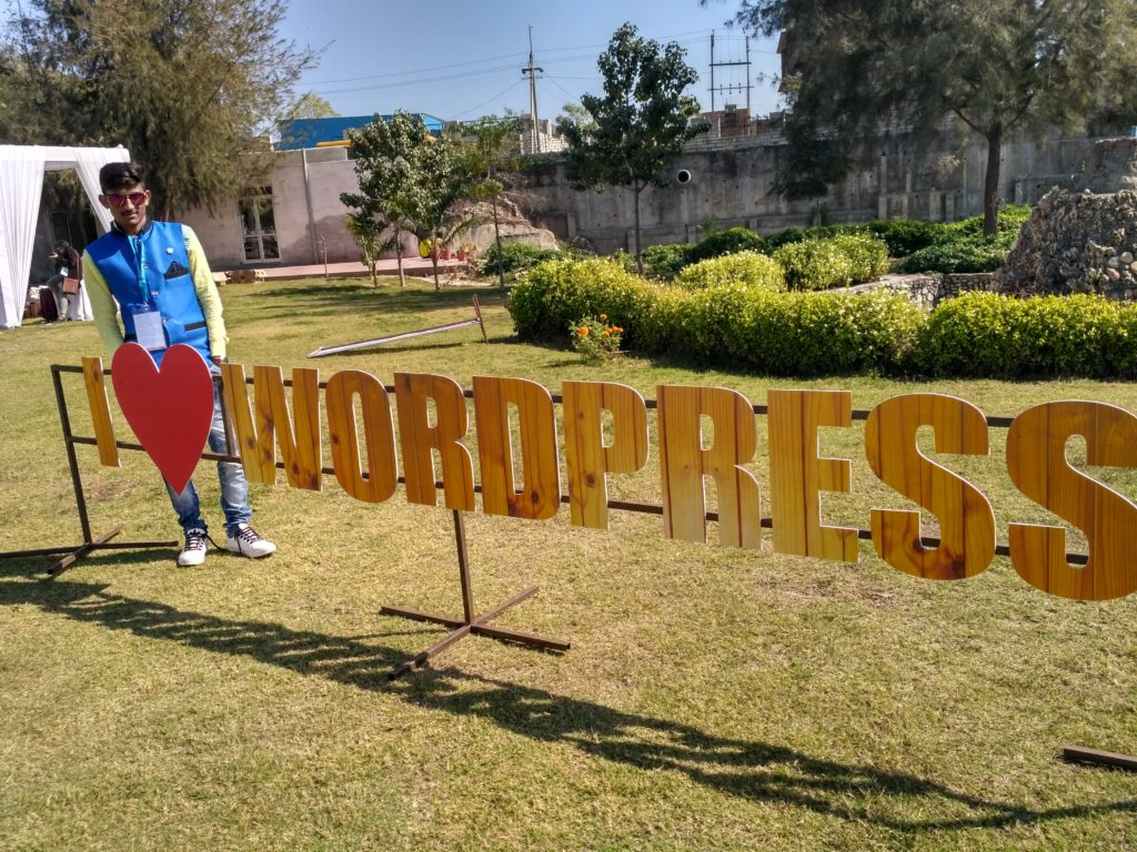 Pravin standing by a long sign that says I Heart WordPress